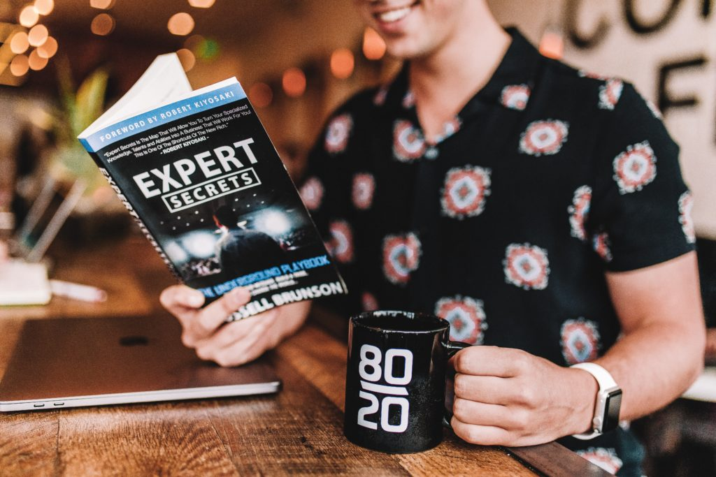 smiling man reading book while holding mug Photo by Austin Distel on Unsplash